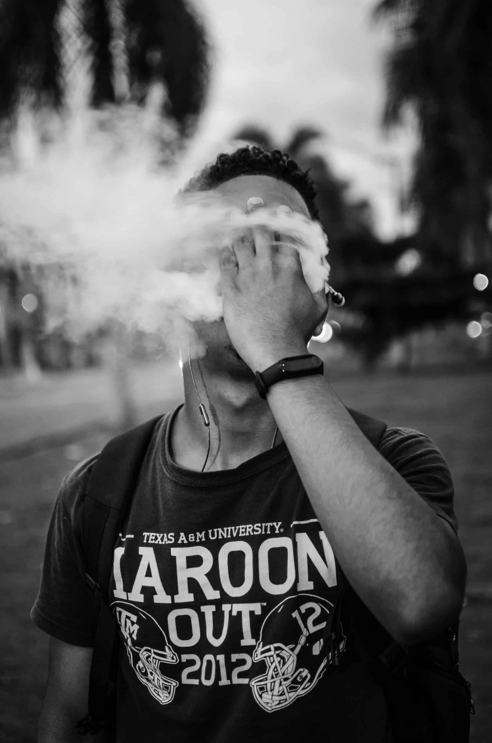 Man covers face while blowing smoke from cannabis weed product